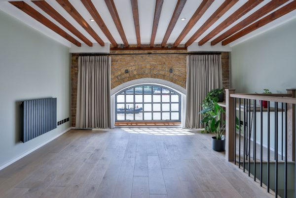 Thames-side flat featuring timber beams, pale green walls, exposed brick and oak flooring. Renovation by Absolute Project Management.