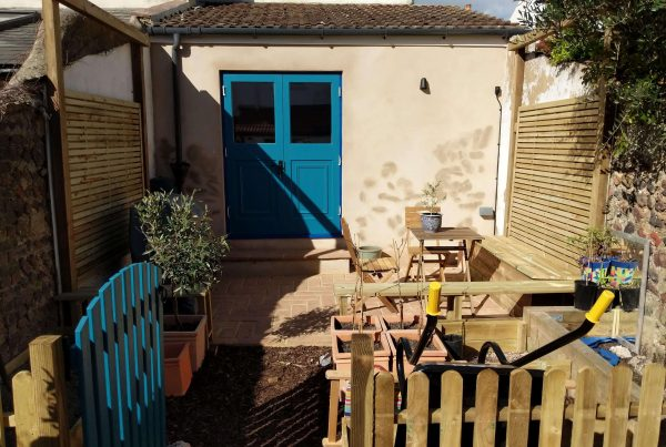 A newly renovated and rendered garden workshop with Marine blue doors. Renovation by Absolute project management.