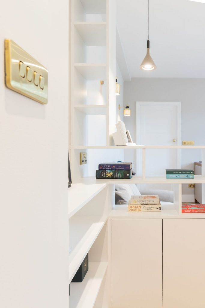 Bespoke open shelving doubles as a room divider, creating storage, display space + a design feature. Renovation by Absolute project Management