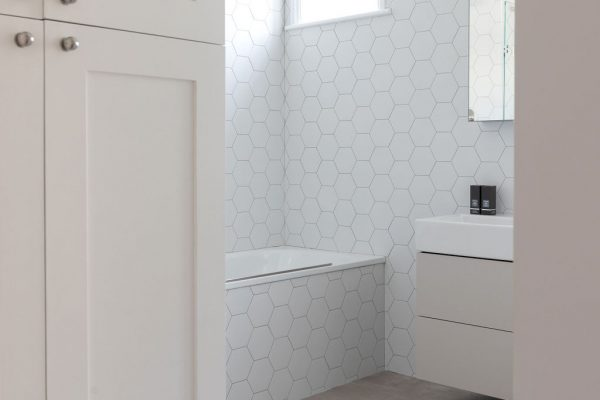 Matt white hexagon wall tiles make this bathroom light and bright, while a taupe Duravit vanity adds a lovely contrast. Renovation by Absolute Project Management.