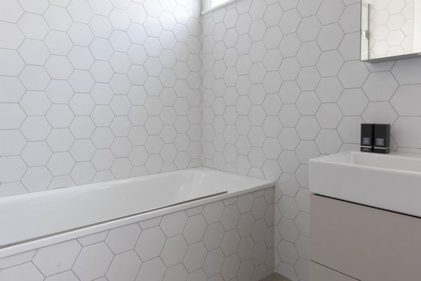Matt white hexagon wall tiles make this bathroom light and bright, while concrete-effect floor tiles add a lovely contrast. Renovation by Absolute Project Management.