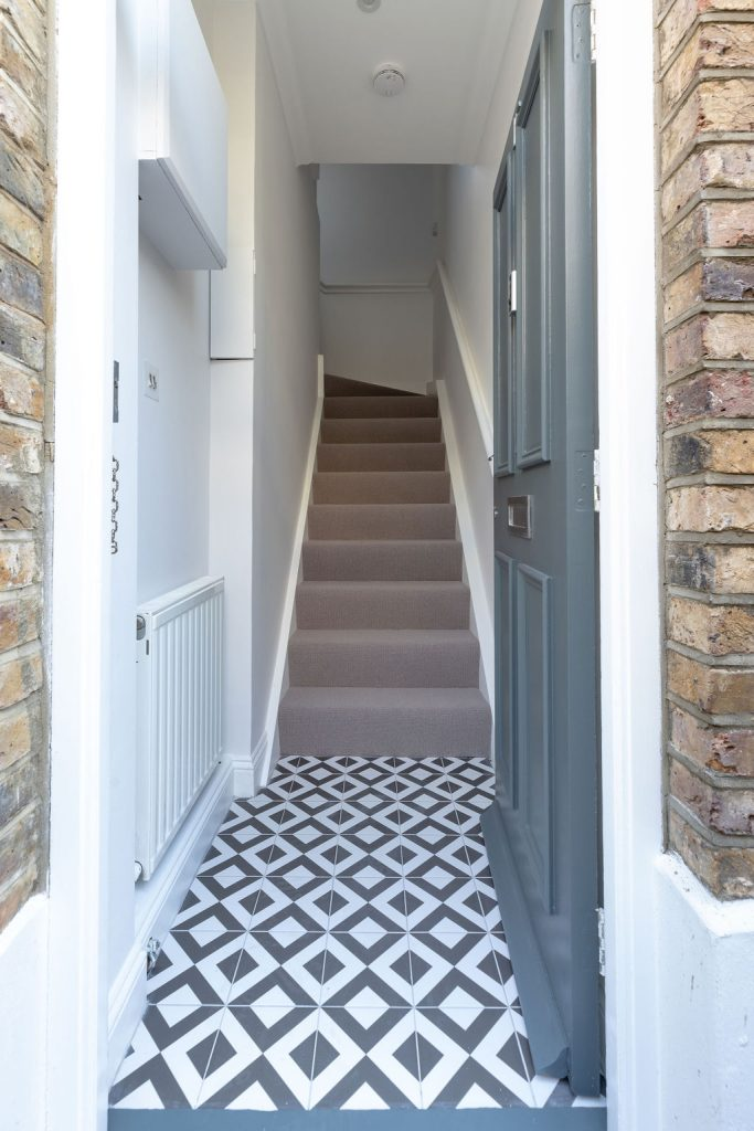 A redecorated staircase with new carpet and fun feature tiles at the entrance create a wonderful welcome into the home. Renovation by Absolute Project Management.