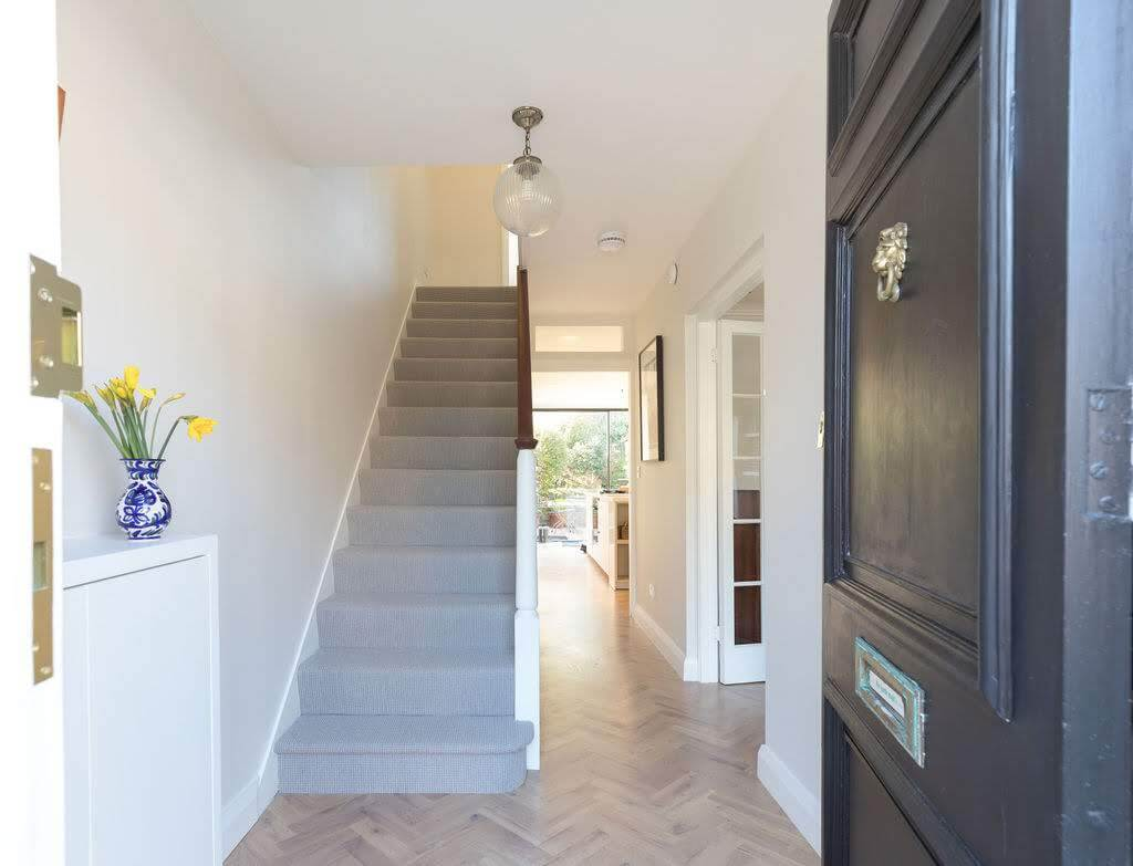 A fun door knocker, some lovely flowers, and stunning parquet makes this entryway warm and welcoming. Renovation by Absolute Project Management.