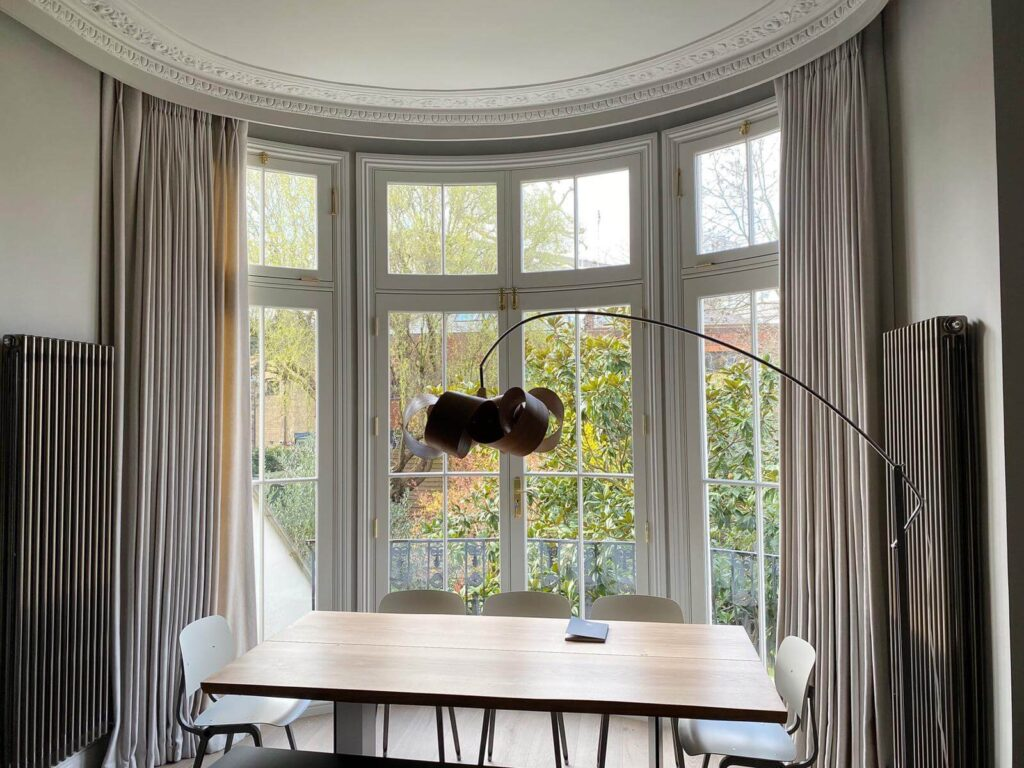 Stunning double-pinch pleat curtain header fitting behind some beautiful ceiling moulding at a bay window. Beautiful feature floor lamp by Tom Raffield. Renovation by Absolute Project Management.